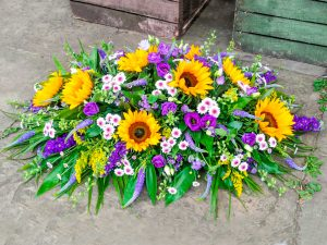 Stunning Coffin Arrangement using Sunflowers, with shades of Lilac and Purple