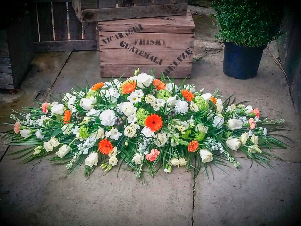 White Coffin Arrangement With Touches Of Orange And Green